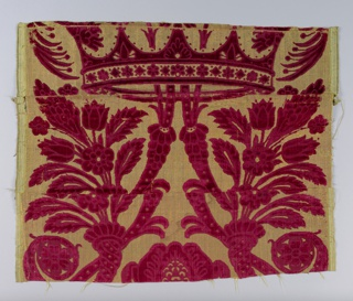 Fragment of a large-scale patterned velvet in red cut and uncut velvet on a gold-yellow ground: cornucopia with bouquet of flowers combined with what seems to be an ogee scroll passing through a crown to enclose a large floral motif.