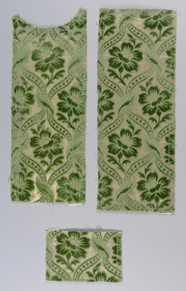 Green flowers within ogival cartouches on a silver metallic background.