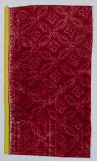 Lattice framing four-petaled flowers on red velvet. Wide yellow selvage.