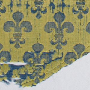 Fragment of woven silk with blue fleur de lys on a yellow ground.
