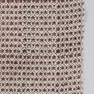 """Fragment of cotton, printed rather sloppily with small all-over trellis-enframing-rosette design, in red and black on natural ground.  To judge from over-lapping, a small block about 2""""x3"""" was used."""