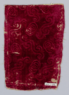 Worn red velvet fragment with stamped (embossed) pattern of detached rings and scrolls,