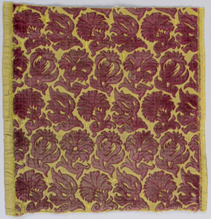 Fragment of red cut and uncut velvet on a yellow ground in a small, tightly-spaced floral pattern.