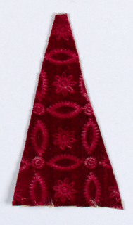 Triangular shaped piece of plain red velvet embossed (stamped) with pattern of ovals and stars.