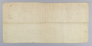 Section of a white table napkin with a broad allover chevron and diamond pattern. Borders have rows of elongated hexagons. Narrow hand hem with linen thread on all sides.