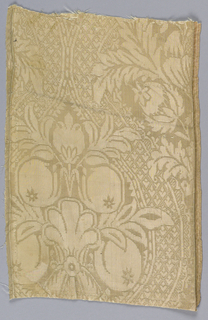 White damask with a design of large medallions containing pomegranates in a patterned ground.