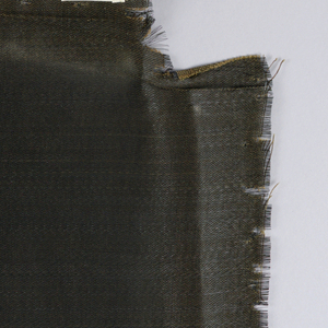 Irregularly shaped pieces with shiny surface. Color appears as rusty black because of a brown warp and black weft. Removed from two chairs belonging to the museum.