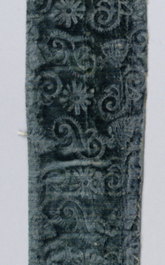 Fragment of blue-green velvet with stamped pattern of 'S' shapes.
