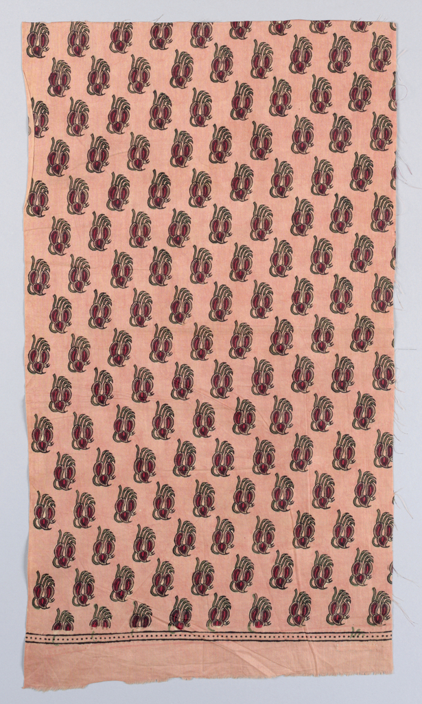 Fragment of cotton block-printed in red, green, black, and touches of brown on rose ground.  All-over pattern of stylized floral form.  Small border stripe made up of black dots.