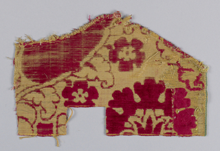 Small irregular-shaped pattern of red cut velvet on a gold metallic cloth ground. Design of large-scale pomegranate pattern.