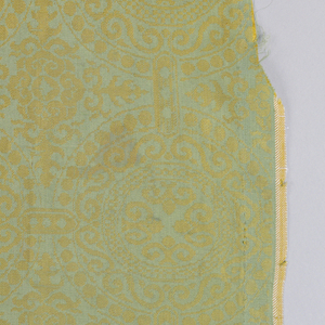 Nineteenth-century copy of a sixteenth-century Italian damask with a green satin ground with yellow silk weft twill patterning. Design consists of large, circular medallions with pearl roundels and S-shaped forms. Medallions connected by shorts bars containing three dots. Quatrefoil motifs between the medallions. Both selvedges present.