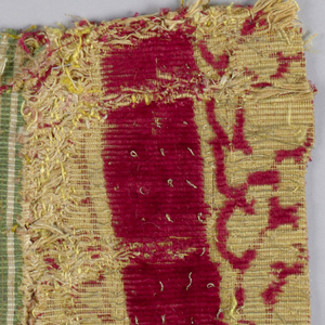 Fragment of woven velvet with pomegranate pattern surrounded by a framework of branches, in red silk pile and gold supplementary weft patterning.