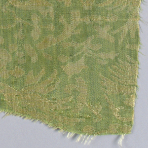 Irregularly shaped fragment with dense pattern of birds and trees in green and pale yellow.