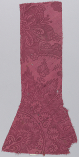 Irregular red fragment with floral pattern.