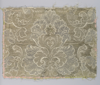 Fragment with a continuous symmetrical pattern reversed on the center line of the fabric. Ornate leaf forms, one on top of the other, surrounded by a leafy scroll frame. Pattern in gold and silver outlined by ivory silk on a gold background.
