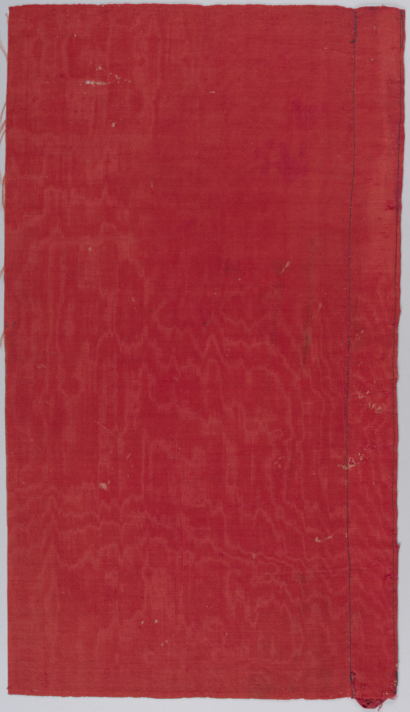 Fragments of red wool, in moire pattern.