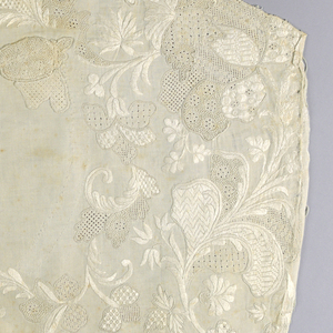 Right side of wite twill waistcoat with deep white embroidered border of scrolling floral and leaf patterns in variety of stitches. Pakcet flap missing and a couple of pieces of white embroidery appliquéed in its place.