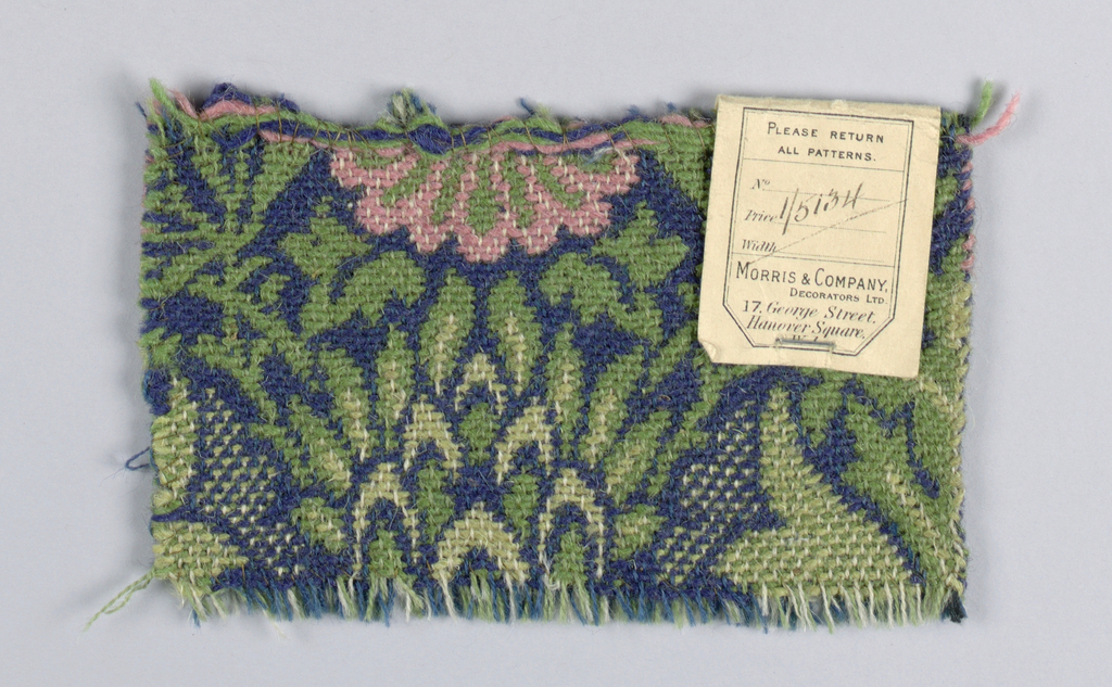 All over floral and leaf pattern of medium scale in shades of green and pink on a dark blue ground. Plain selvage with black warps.