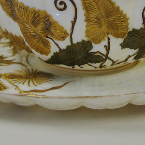 "Extremely thin, transparent white body moulded in ridges resembling a scallop shell. Relief decoration in green and gold.  On cup, a bunch of leaves and a butterfly, on saucer a thistle plant.  Marked ""BELLEEK"" in rust brown on cup and saucer."