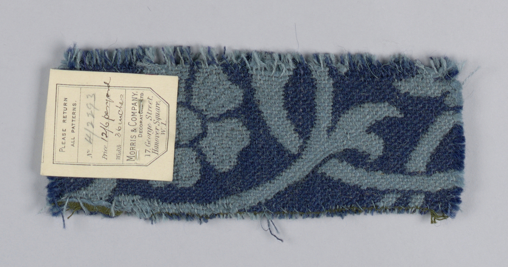 Carpet fragment similar in style to the Kidderminster or Ingrain type. Pattern is a medium-scale allover symmetrical floral and leaf pattern in soft blue on deeper blue ground.