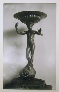 Vertical rectangle. The nude figure of a boy, standing, faces the viewer. The arms are upraised. He carries a basin on his head and stands on a pedestal in the form of a vessel with a grotesque head.