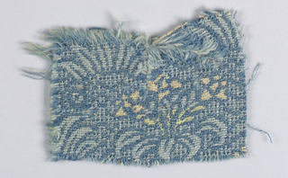 Small fragment of wool tabby showing pattern of a lily in shades of pink, yellow, and light blue against a darker blue background.