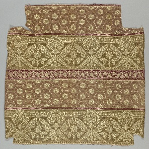 Fragment of woven upholstery fabric with a design of alternating pattern bands: flowers in hexagonal tiles in gold on terra cotta, stylized palmette pattern in gold on olive green, narrower bands of egg and dart pattern in gold on maroon.
