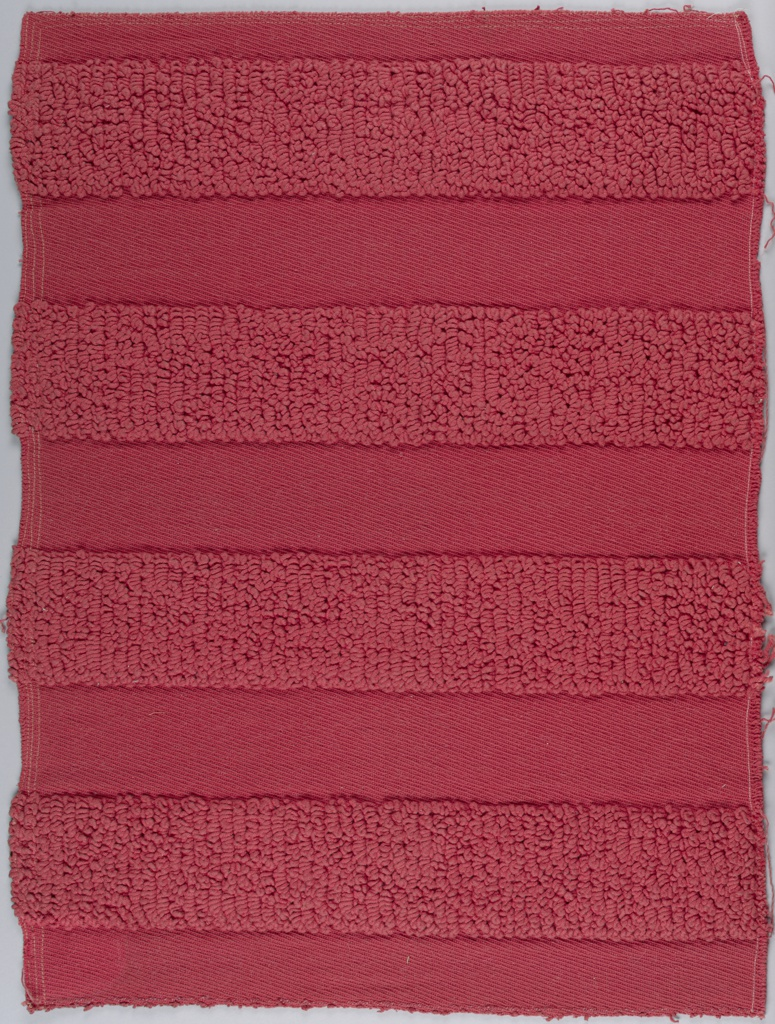 Deep coral textile with broad vertical stripes of two contrasting textures used alternately. One is formed of deep close set warp loops of heavy multi-plied cotton; the other is in a novelty warp twill with S-plied cotton warps. Wefts are S-spun and have a thin piece of undyed wool twisted around each.