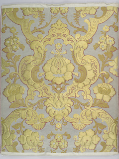 Sample of material woven for the Russian church. Silver ground with symmetrical design of central formalized blossom framed with rococo curves and acanthus leaves in gold and silver brocade with outline of dark red silk.