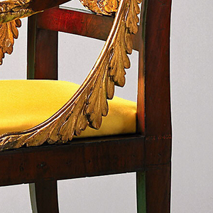 Mahogany armchair with square tapering front legs which curve inwards.  The plain mahogany top rail has beneath it a carved wreath of oak leaves which forms the slat.  The seat is upholstered and covered in red silk, with gold embroidered medallion in center.  The arms are carved and terminate in eagle heads.  The arm supports are formed by lions paw feet.  Two festoons of oak leaves rise from the arms to the seat rail.  All the carving is gilded.