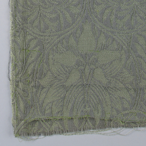 Allover pattern formed by close-set diagonal repeat of flower and leaf bouquet in curling stems with smaller circles formed tangent below it on either side. In matte gray-blue wool on shiny soft yellow-green mohair ground.