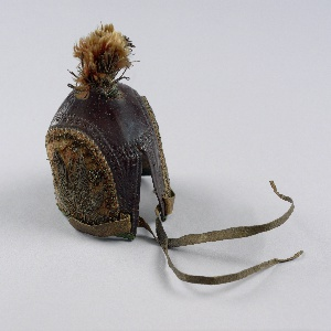 Brown tooled leather hood shaped to fit the head of a falcon. The sides are decorated with panels of rose red velvet embroidered with silver metallic yarns and faceted metal beads. At the top, a tassel of rose red silk is bound in silver metallic yarn. The edges are bound with green silk braid. With leather tabs for fastening.