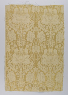 Upholstery fabric of unbleached linen woven with gold silk in a design of formalized flowers and leaves arranged in vertical stripes.