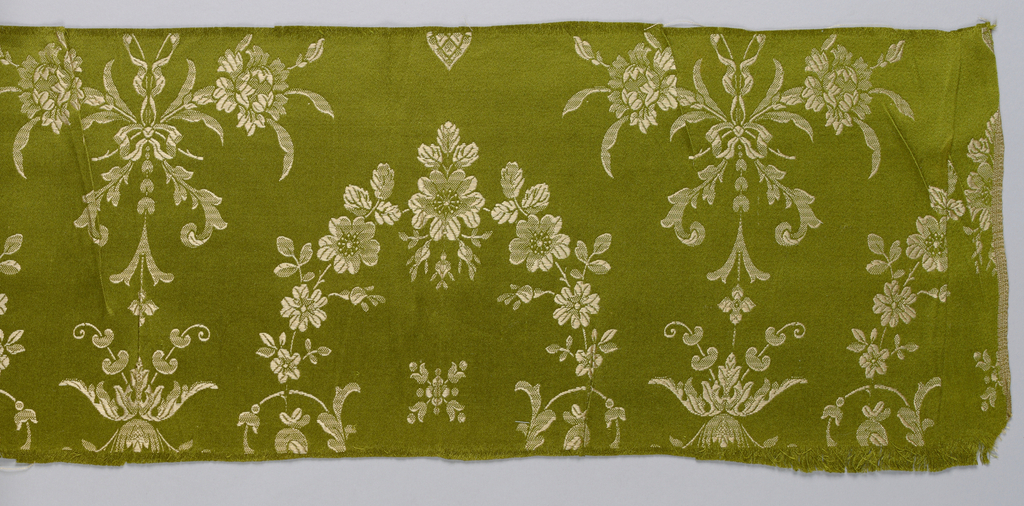 Green warp and gold color weft forming floral pattern.
