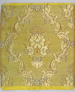 Sample of material woven for the Russian church. Symmetrical design of central formalized group of flowers surrounded by serpentine rococo curves, acanthus leaves, grapes and flowers. Ground of gold. Design of gold and silver in high relief.