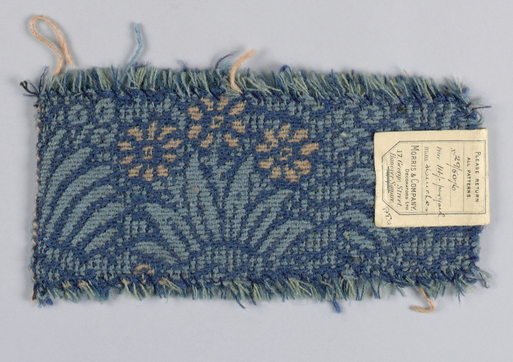 Carpet fragment with a medium-scale allover flower and leaf repeat in delft blue, light blue and pale coral. One plain selvage with black cotton warps.