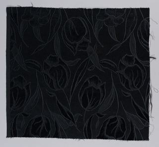 Fragment of jacquard, hand-cut satin showing life-size tulips in black on black. Areas filled with velvet. Pattern reversible.