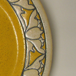 Dish with bright yellow well; border of flattened natural-colored blossoms outlined in thick black on yellow ground.