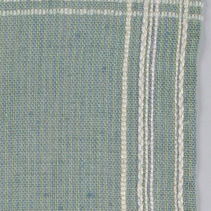 Placemat in tan, blue and green with heavier white floss forming uneven borders of narrow stripes on all four sides.