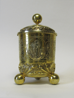 Cylindrical cup on three ball feet. Lower part, repousse shells and leaves; upper two thirds engraved with strapwork and scrolls with masks of crowned woman, turbaned, bearded man and faun. Three engraved ovals, with woman standing amidst waves (Aphrodite), a fairy-like winged woman, faun with thunderbolt.  Domed cover with repousse band of shells and leaves, and ball knob.
