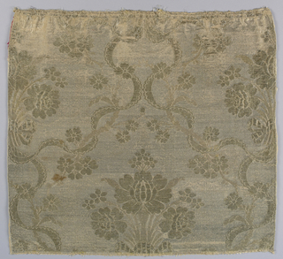 Peach and metallic silver fabric in a design of a large-scale central spray of roses flanked by scalloped ribbon serpentines meeting in the center. Large roses in high relief. Metallic brocading in several kinds of gold thread.