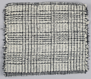 Warp: black and white Rovana, Weft: black rovana and ivory asbestos. Bands of double cloth alternating with bands of plain weave textured with three span floats. Note change in the alternation of warp colors.