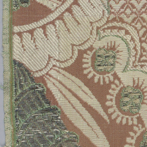 Fragment of brocaded silk damask. Pink and cream ground with details brocaded in metallic yarns and yellow, green and white silk, showing closely spaced florals and lace pattern.