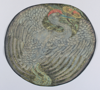 Slightly oval medallion filled by a light blue crane with out-stretched wings holding a flower or fungus in its beak. Bird superimposed on gold scrolls (clouds) on a black background.