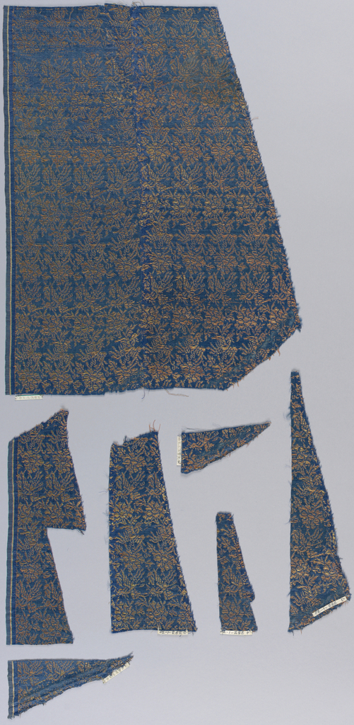 Dense, small-scale pattern of alternating bird and floral motifs in blue and gold.
