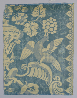 Blue and white textile fragment made of two mirrored pieces. Design showing exotic birds flanking an urn and eating from a fruit vine.  A border design at each selvage.