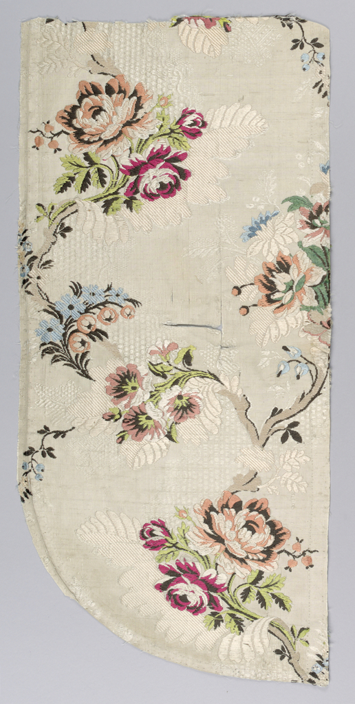 Serpentine pattern of polychrome branches on off-white. Many tears in the fabric.