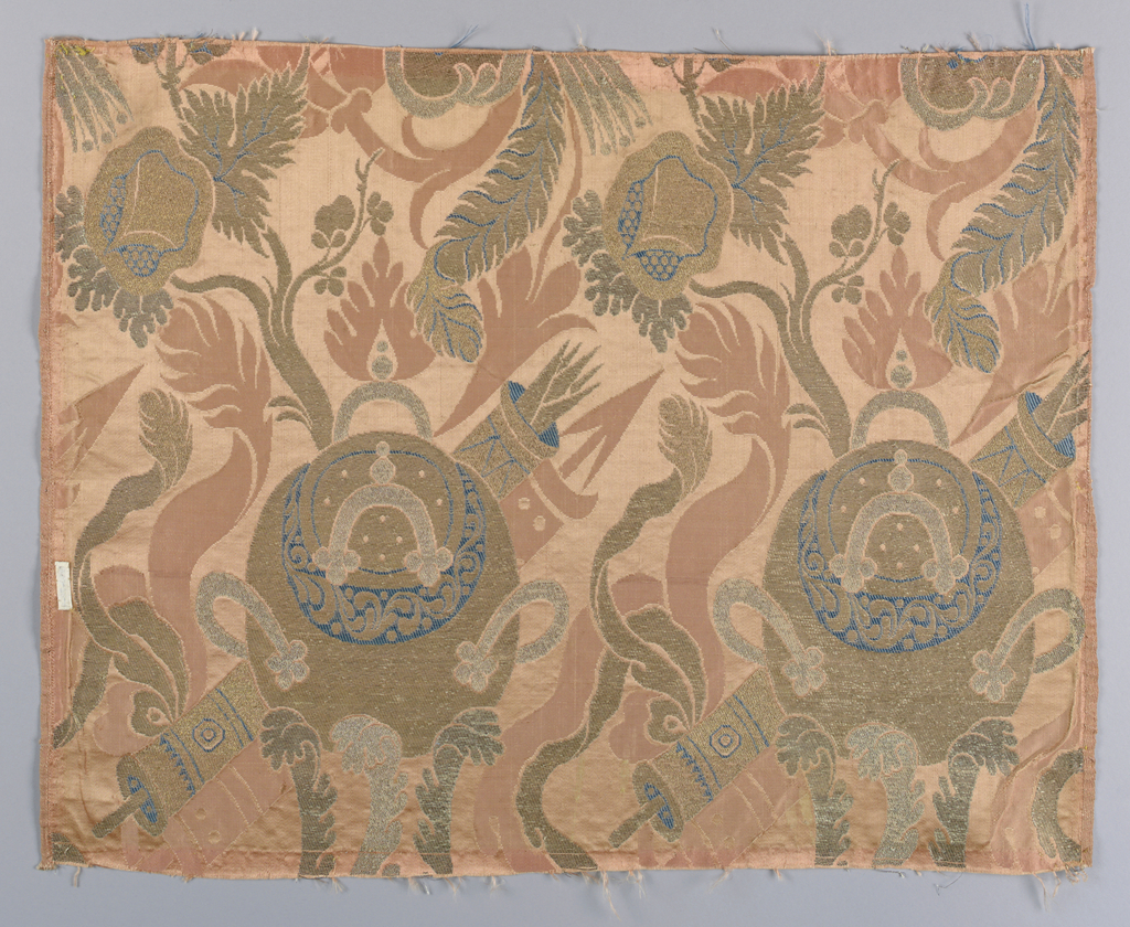 Coral colored damask fragment brocaded with blue silk and metallic yarns. Design in the 'bizarre' style shows a pattern of a large round pot superimposed on a long diagonal cylinder with elongated leaf shapes. Both selvages present.