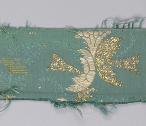Metallic gold chinoiserie sprays on green ribbed ground brocaded in both gold strips and gold wound on cream silk core