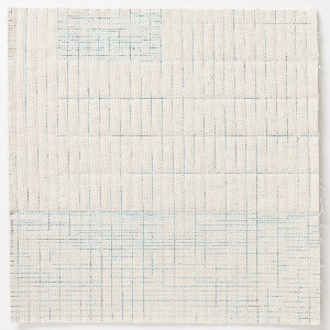 Two pieces of off-white canvas are machine stitched using in blue thread making a pattern of grids and lines. Fiberfill between the pieces.